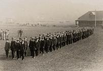 Photograph of recruits to the 18th Battalion, The Durham Light Infantry, in civilian dress, being drilled on Durham racecourse, n.d., [September 1914] (D/DLI 2/18/26)