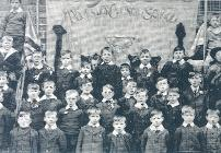 Photograph of boys from Thornley Council Boys School with a memorial banner bearing two black bows, 1916 (D/Ph 150/39)